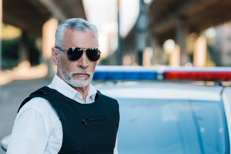 portrait of confident middle aged policeman in sunglasses and bulletproof vest near car at street Imagens