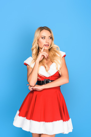 thoughtful sexy santa girl in christmas dress with finger near mouth isolated on blue background