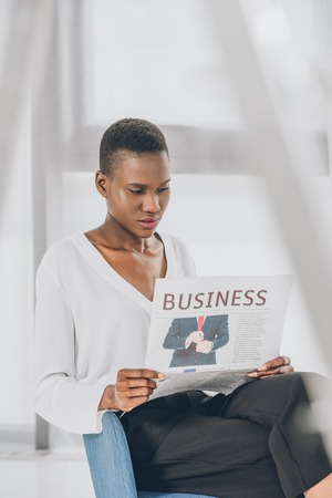 stylish attractive african american businesswoman reading newspaper in armchair in office