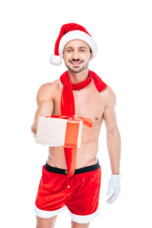smiling shirtless muscular man in christmas hat and red scarf giving present isolated on white background Stock Photo
