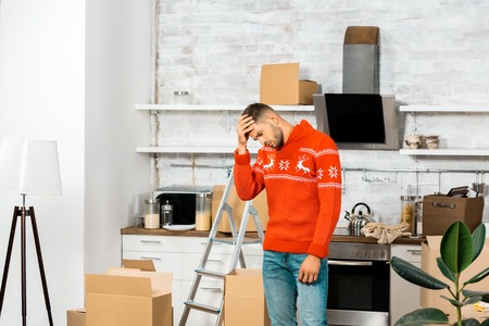 upset young man holding forehead in kitchen with cardboard boxes during relocation in new home