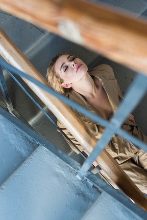 overhead view of beautiful blond woman in trench sitting on steps