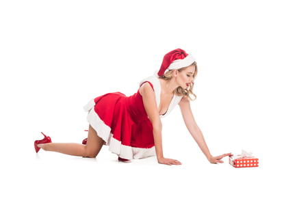 seductive santa girl in christmas dress on all fours near gift box isolated on white