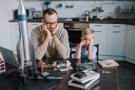 pensive father and son looking at circuit board on table at home Standard-Bild