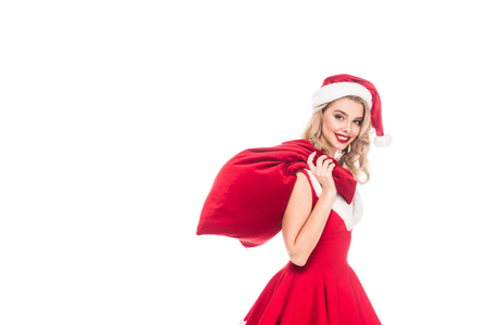 happy young woman in santa dress holding christmas sack over shoulder isolated on white Stock Photo