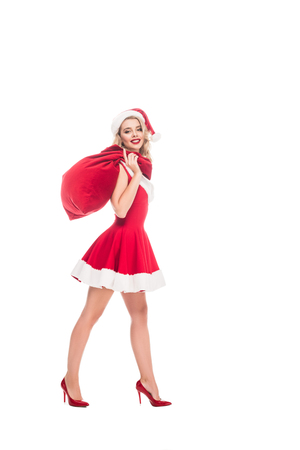 cheerful young woman in santa dress holding christmas sack over shoulder isolated on white Stock Photo