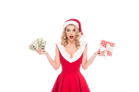 surprised santa girl in christmas hat holding cash money and gift box isolated on white