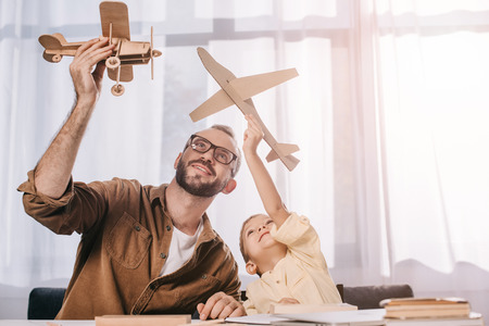 happy father and little son playing with wooden planes models at home Stockfoto