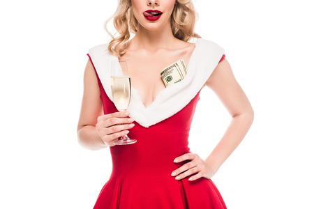 partial view of seductive sant girl with cash money holding champagne glass and licking lips isolated on white