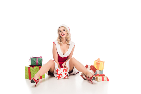 sexy santa girl in christmas dress sitting on floor with pile of gift boxes isolated on white Stock Photo