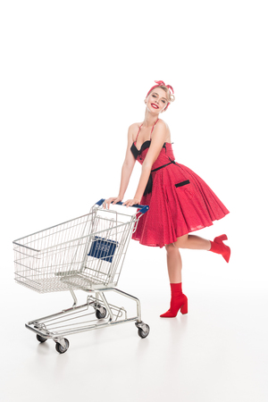 happy young woman in retro pin up dress carrying shopping cart isolated on white