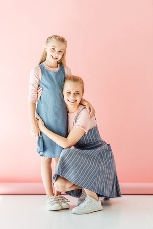 smiling mother sitting squats and embracing her daughter on pink and looking at camera