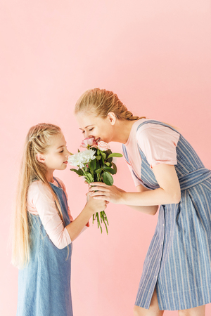 happy young mother and daughter sniffing bouquet together isolated on pink Imagens - 110255855