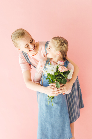 smiling young mother and daughter holding beautiful bouquet and looking at each other isolated on pink