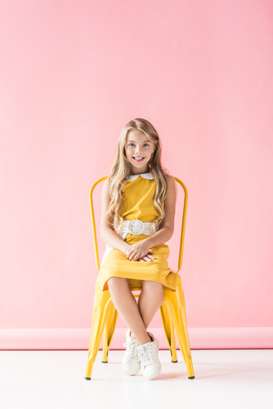 happy fashionable adorable youngster sitting on yellow chair on pink Stock Photo