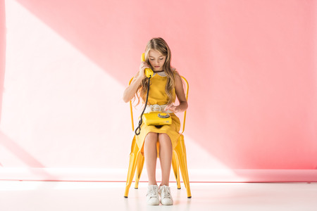 fashionable kid making call on retro phone while sitting on yellow chair on pink Foto de archivo