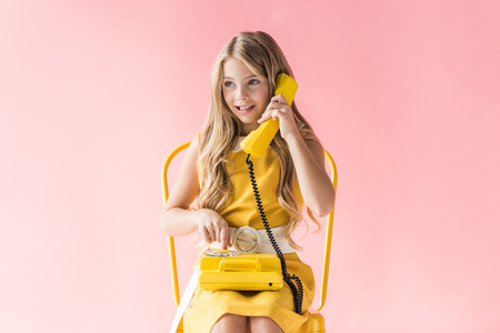 adorable smiling child making call on yellow rotary phone while sitting on chair on pink