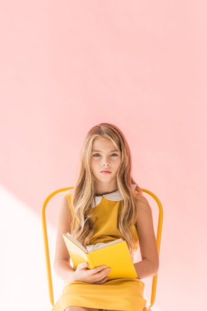 fashionable youngster reading book while sitting on yellow chair on pink Foto de archivo