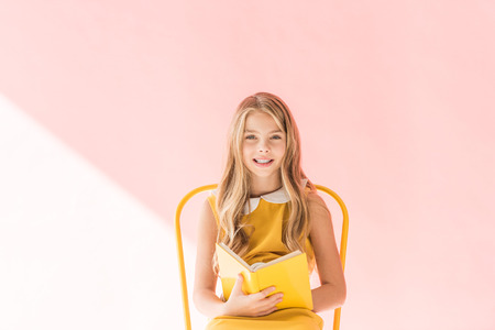 smiling kid reading book while sitting on yellow chair on pink Archivio Fotografico