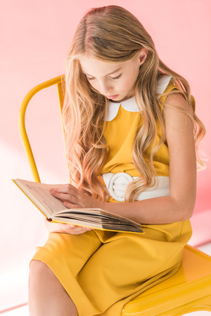 stylish blonde youngster reading book while sitting on yellow chair on pink Foto de archivo