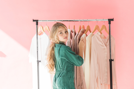 attractive female child in trendy overalls choosing clothes on hangers