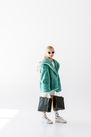 charming kid in trendy fur coat and sunglasses posing with black shopping bags on white