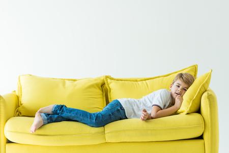 entzückender Junge, der in Freizeitkleidung auf gelbem Sofa liegt, isoliert auf weiß