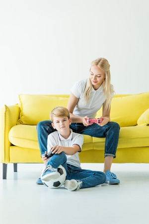 mother looking at son while playing video game on yellow sofa on white, football ball on floor