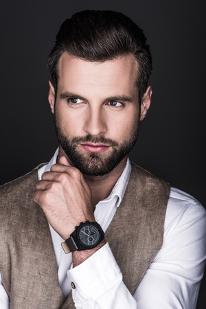 portrait of elegant bearded man with wristwatch, isolated on grey 스톡 콘텐츠