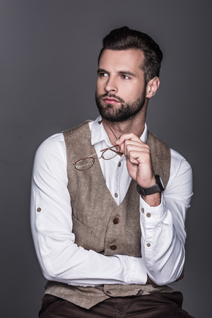 portrait of handsome bearded man holding glasses and posing in waistcoat, isolated on grey 스톡 콘텐츠