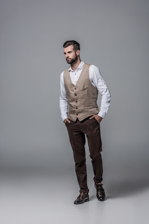 handsome bearded man posing in trendy elegant waistcoat on grey 스톡 콘텐츠