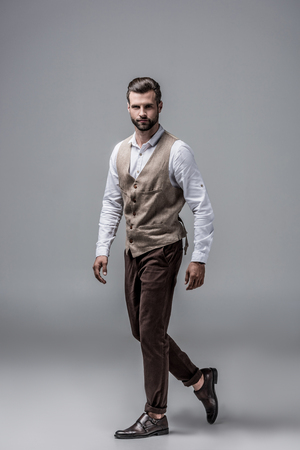 handsome elegant man posing in stylish vest for studio shot on grey