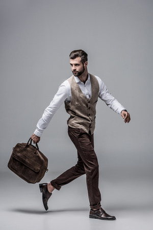 hurry stylish man running with leather bag on grey 스톡 콘텐츠