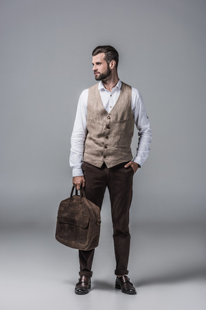 stylish elegant man in waistcoat posing with leather bag on grey Stock Photo