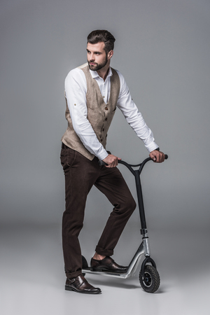 stylish elegant young man posing on modern scooter on grey 스톡 콘텐츠