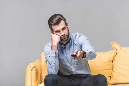 Apuesto hombre aburrido con control remoto viendo la televisión en el sofá amarillo sobre gris
