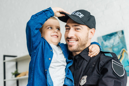 close-up portrait of smiling young father in police uniform carrying his little son and looking at camera Stockfoto