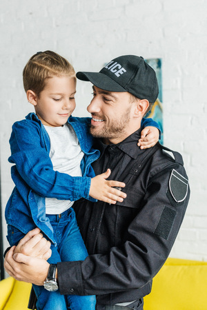 handsome young father in police uniform carrying his little son Zdjęcie Seryjne