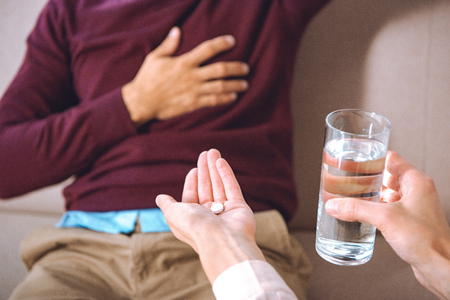 cropped shot of psychotherapist giving glass of water and pill to patient with heartache