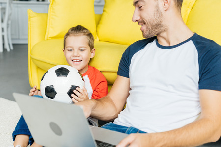 man using laptop while little son with football ball sitting near by on floor at home