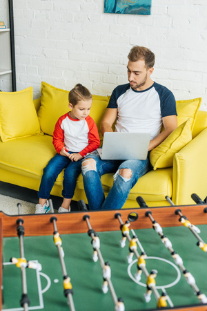 father and son using laptop together while resting on yellow sofa at home