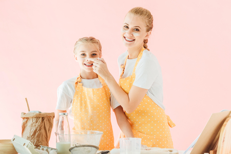 smiling mother and daughter with flour on faces looking at camera while cooking isolated on pink Banque d'images