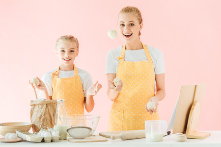 happy mother and daughter juggling with dough pieces while cooking isolated on pink