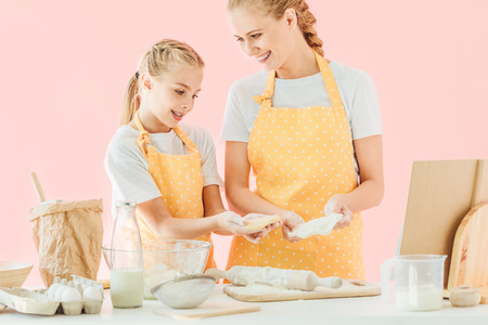 happy young mother and cute little daughter preparing dough together isolated on pink Banque d'images