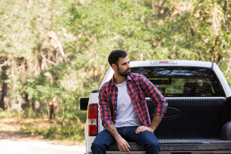 confident bearded man sitting on pickup truck in forest
