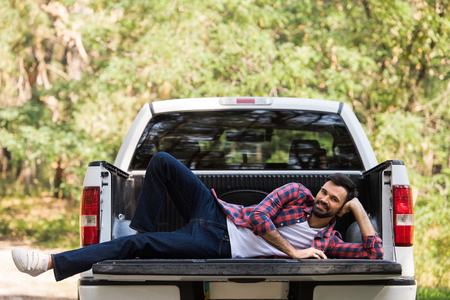 happy bearded man relaxing on pickup truck in forest Stock Photo