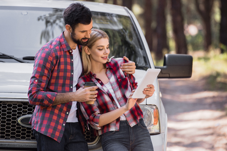 couple hugging and using digital tablet near pickup truck in forest