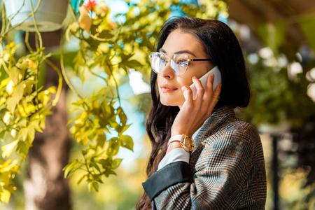 beautiful stylish woman in eyeglasses talking on smartphone 스톡 콘텐츠 - 110294778