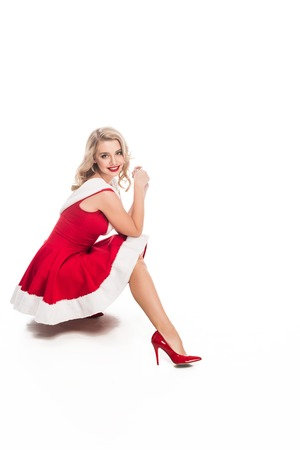 beautiful santa girl in christmas dress sitting isolated on white