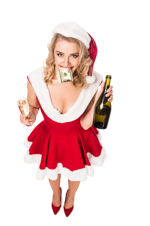 high angle view of attractive santa girl in christmas dress with money in mouth holding champagne bottle and glass isolated on white